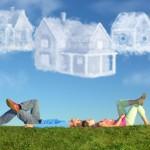 Über einem Paar, das auf der Wiese liegt, schweben Wolken in Form von Häusern